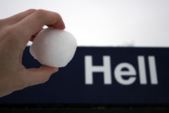 Like a snowball in hell. A hand holding a snowball in front of a sign saying hell. refering to the frace like a snowball in Hell Royalty Free Stock Image