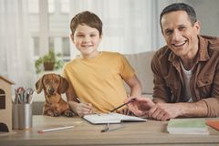 Excited man and boy drawing with joy. We like spending time together. Portrait of glad father and son doing arm together at home near interested dog Stock Image
