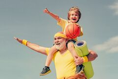 Like sports. Joyful old-aged man and cute little boy practicing sport and healthy lifestyle over sky background. Fathers