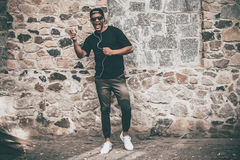 Like a star. Full length of handsome young African man in headphones singing and gesturing while standing against the stoned wall outdoors Stock Images