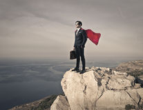 Like a superhero. A businessman on the top of a rock like a superhero royalty free stock images
