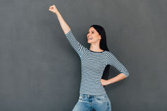 Like a superhero. Happy young woman stretching out hand like superhero and smiling while standing against grey background royalty free stock photography