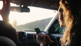 We like to travel. A young woman with a phone rides in the front passenger seat of the car. In the rays of a setting sun stock footage