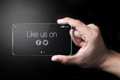 Like us on Facebook and Twitter. Johor, Malaysia - Transparent smartphone, like us on Facebook and twitter icon with hand on dark background. Facebook and royalty free illustration