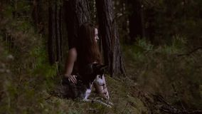 Likely girl sitting in nature with her wolf-looking dog. They look around and are concentrated. Slow motion stock video footage