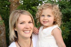 Likeness. Young attractive woman holding her pretty blond daughter outdoors and looking at camera Stock Images