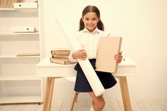 She likes creative tasks. Girl child hold folder and whatman paper while stand table white interior. Kid school uniform stock photo