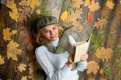 She likes detective genre. Girl blonde lay wooden background with leaves. Woman lady in checkered hat and scarf read. Book. Girl in vintage outfit enjoy stock photos