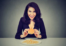 She likes fast food. Happy young woman eating cheeseburger and french fries Royalty Free Stock Photos