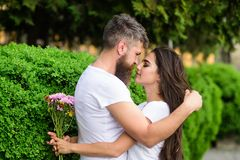 He likes her gorgeous hair. Girl holds flowers while man caress her long hair. Couple in love hugs outdoors park. He likes her gorgeous hair. Girl holds flowers royalty free stock photography