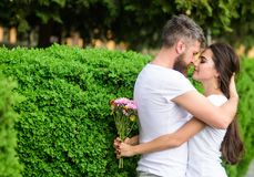 He likes her gorgeous hair. Man bearded hipster gently hugs girlfriend enjoying her soft long hair. Couple in love hugs. Outdoors park background. Girl holds stock images