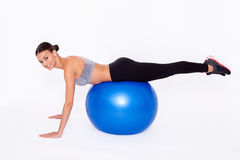 She likes to look good. Shot of attractive woman balancing on an exercise ball with smile over white background Stock Photo