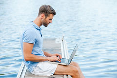 He likes to work outdoors. Side view of handsome young man in polo shirt working on laptop while sitting on quayside Royalty Free Stock Photos