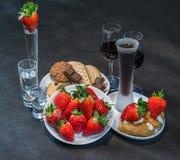 Likeur en wodka in glazen, aardbeien en koekjes met pastei royalty-vrije stock afbeeldingen