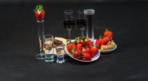 Likeur en wodka in glazen, aardbeien en koekjes met pastei stock foto's