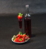 Likeur in fles en in glas met aardbeien, aardbeien royalty-vrije stock foto's
