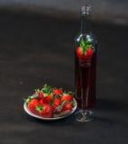 Likeur in fles en in glas met aardbeien, aardbeien royalty-vrije stock foto