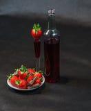 Likeur in fles en in glas met aardbeien, aardbeien stock afbeelding
