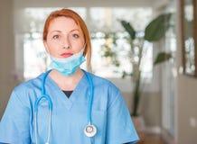 Likformig för sjuksköterska för ung härlig rödhårig mankvinna bärande arkivbilder