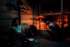 Liki en een andere stammenjongen bereiden het diner in hun wildernis voor ho stock fotografie
