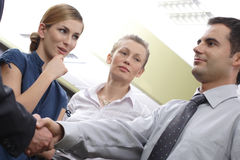 Liking The New Guy. Male business employee shaking the hand of an unseen male employee, while two female employees, one with great interest, look on. In an stock images