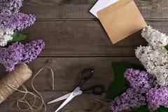 Lila Blüte auf rustikalem hölzernem Hintergrund mit leerem Raum für Grußmitteilung Scheren, Threadspule, kleiner Umschlag Lizenzfreies Stockfoto