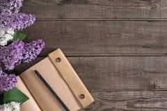 Lila Blüte auf rustikalem hölzernem Hintergrund mit Notizbuch für Grußmitteilung Beschneidungspfad eingeschlossen Lizenzfreies Stockfoto