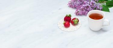 Lila Blütenniederlassungen, Tasse Tee und Erdbeeren auf Carrara m Stockfoto