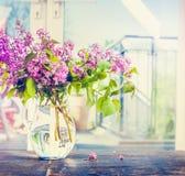 Lila blommor samlar ihop i den glass vasen på fönster fortfarande, inomhus Royaltyfri Foto
