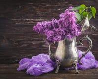 Lila Blumen in der dekorativen Weinleseteekanne Stockfoto