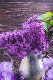 Lila Blumen in der dekorativen Weinleseteekanne Stockfotos