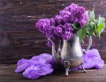 Lila Blumen in der dekorativen Weinleseteekanne Stockbild