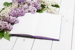 Lila Blumen mit Notizbuch auf dem hölzernen Hintergrund Stockbild