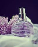 Lila Blumen nahe einer Flasche Parfüm Stockfotografie