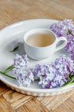 Lila Blumenblumenstrauß, hölzerner Schreibtisch, weißer Hintergrund, Morgen Stockfotos