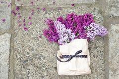 Lila Blumenstrauß in einer Papiertüte gebunden mit einem schönen Band Stockbilder