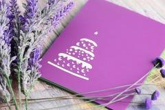Lila Grußkarte mit Platz für Text und Lavendel blüht auf einem hellen hölzernen Hintergrund Lizenzfreies Stockfoto