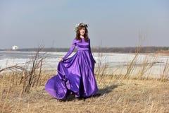 Lila Kleid der Frau mit einem Kranz von Blumen auf ihrem Kopf auf Natur Lizenzfreie Stockfotografie