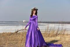 Lila Kleid der Frau mit einem Kranz von Blumen auf ihrem Kopf auf Natur Stockfotos