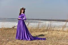Lila Kleid der Frau mit einem Kranz von Blumen auf ihrem Kopf auf Natur Lizenzfreie Stockfotos