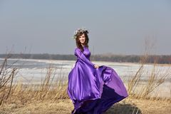 Lila Kleid der Frau mit einem Kranz von Blumen auf ihrem Kopf auf Natur Lizenzfreie Stockbilder