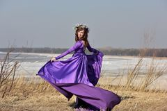 Lila Kleid der Frau mit einem Kranz von Blumen auf ihrem Kopf auf Natur Stockfoto
