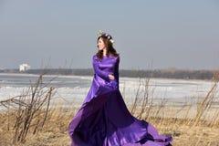 Lila Kleid der Frau mit einem Kranz von Blumen auf ihrem Kopf auf Natur Lizenzfreies Stockbild