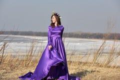Lila Kleid der Frau mit einem Kranz von Blumen auf ihrem Kopf auf Natur Lizenzfreies Stockfoto