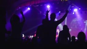 Lila Licht auf Stadium - viele Leute, die am Konzert tanzen stockbild