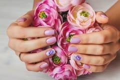 Lila Nagelkunst mit Druckblumen auf hellem Hintergrund Lizenzfreie Stockbilder
