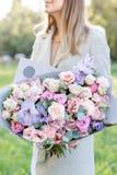 Lila och rosa pastellfärgad härlig vårbukett Ung flicka som rymmer en blommaordning med olika blommor brigham royaltyfri bild