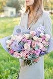 Lila och rosa pastellfärgad härlig vårbukett Ung flicka som rymmer en blommaordning med olika blommor brigham royaltyfri foto