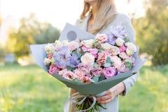 Lila och rosa pastellfärgad härlig vårbukett Ung flicka som rymmer en blommaordning med olika blommor brigham arkivbilder