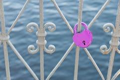 Lila slott i formen av en hjärta på metallstängerna av bron Royaltyfri Fotografi